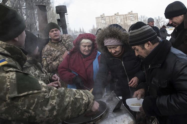 Des soldats ukrainiens servent des repas à deshabitants... (PHOTO AP)