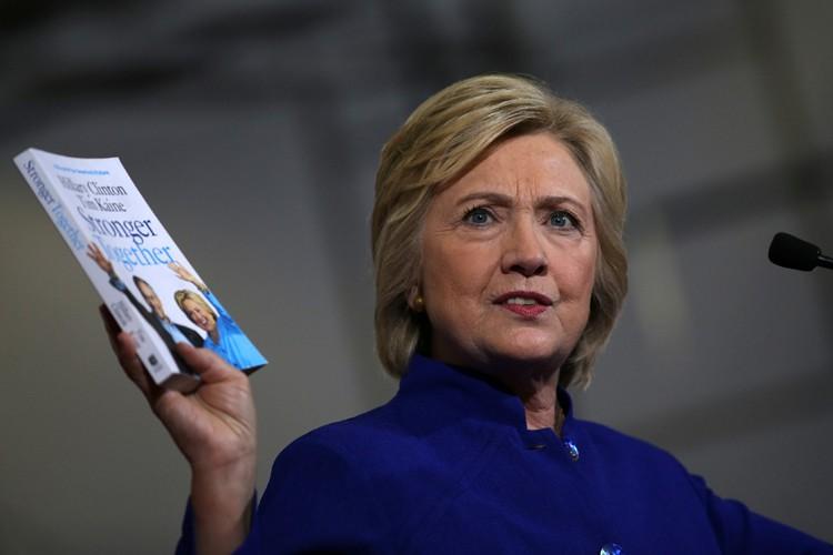 Hillary Clinton brandit une copie de son livre... (PHOTO REUTERS)