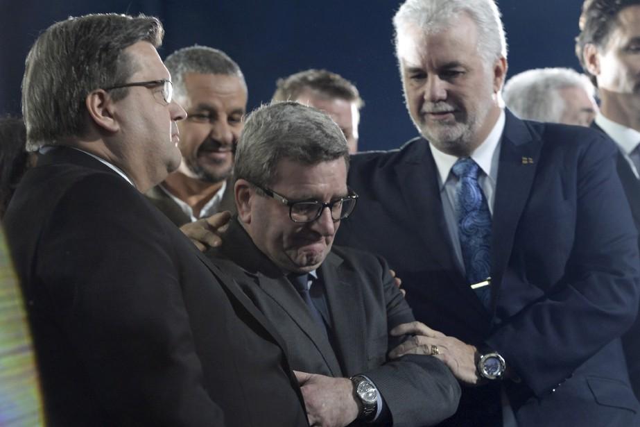 Denis Coderre regarde la cérémonie, pendant que Régis Labeaume est réconforté par Philippe Couillard. (La Presse Canadienne, Paul Chiasson)