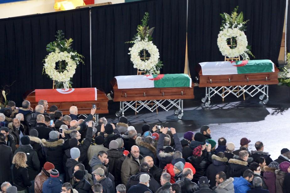 Dans un coin de la patinoire, recouverte d'un plancher de bois noir pour l'occasion, trois cercueils étaient alignés. Le drapeau d'Algérie recouvrait ceux de Khaled Belkacemi, 60 ans, professeur au Département des sols et de génie agroalimentaire de l'Université Laval, et d'Abdelkrim Hassane, 41 ans, analyste programmeur au Centre de services partagés du Québec. Le cercueil d'Aboubaker Thabti, 44 ans, chef d'équipe chez Exceldor, était plutôt drapé des couleurs de la Tunisie. (AFP, Paul Chiasson)