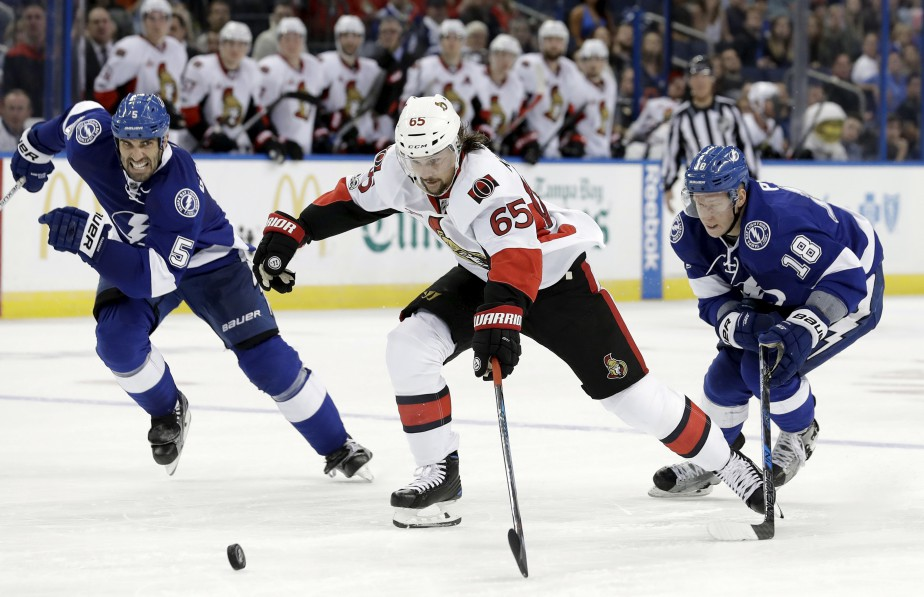 Erik Karlsson, Jason Garrison et Ondrej Palat luttent pour la rondelle. (Chris O'Meara, Associated Press)