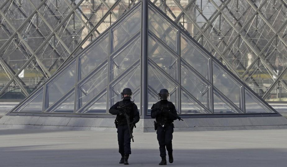 Des policers patrouillent près de la pyramide du Louvre. (Photo Christian Hartmann, REUTERS)