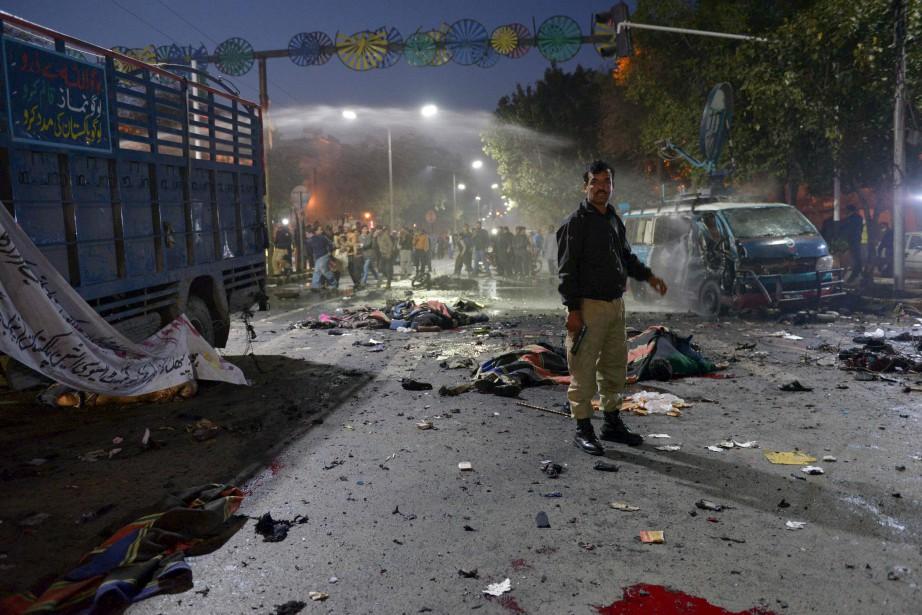 Un policier pakistanais tient la garde, entouré des victimes d'une... | 2017-02-13 00:00:00.000