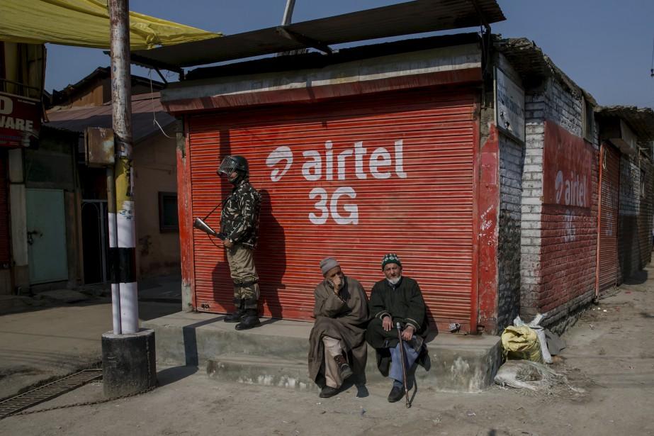 Un soldat paramilitaire indien tient la garde aux portes d'un marché fermé, alors que des Cachemiris se prélassent au soleil matinal. Les commerces sont restés fermés depuis samedi après que des séparatistes aient appelé à une grève suite au combat qui a emporté quatre présumés rebelles et deux soldats indiens. | 13 février 2017