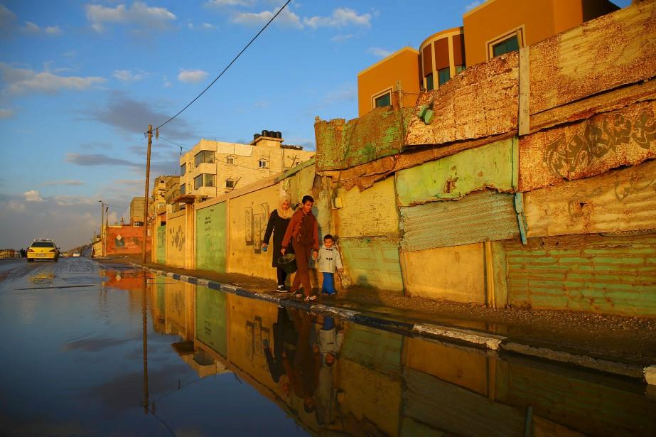 Des Palestiniens marchent le long d'une rue inondée après la tempête qui a pris d'assaut le camp de réfugiés d'Al-Shatee à Gaza. | 13 février 2017