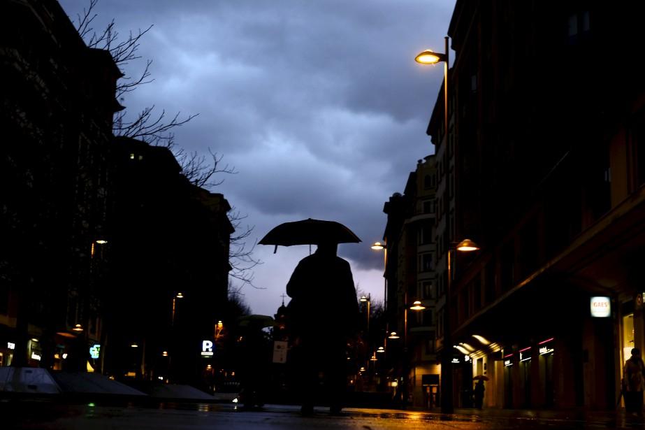 Un homme s'abrite d'un parapluie en marchant sous une pluie hivernale à Pampelune, en Espagne. | 13 février 2017