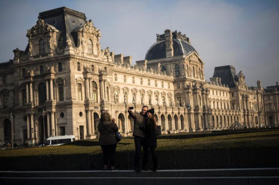Des touristes prennent une photo devant le Musée... (photo LIONEL BONAVENTURE, ARCHIVES AGENCE FRANCE-PRESSE)
