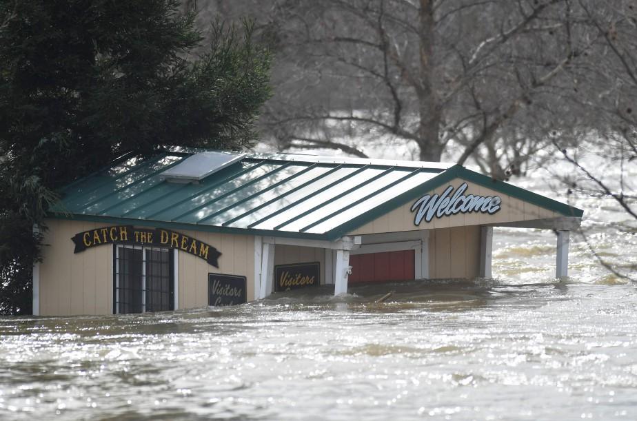 Un bâtiment est submergé par le courant au Parc Riverbend, en Californie, alors que le barrage d'Oroville continue de relâcher plus de 100 000 pieds cubes d'eau par seconde afin de réduire le niveau du Lac Oroville qui est à 101% de sa capacité. Plus de 100 000 personnes ont été évacuées des régions environnantes après que l'érosion eut endommagé le couloir d'urgence du barrage. | 14 février 2017