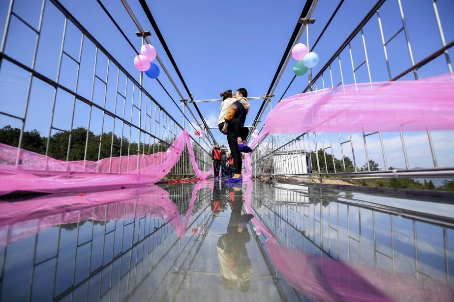 Un couple chinois s'embrasse sur un pont de verre, lors d'un concours de bisou pour la Saint-Valentin à PingJiang. | 14 février 2017