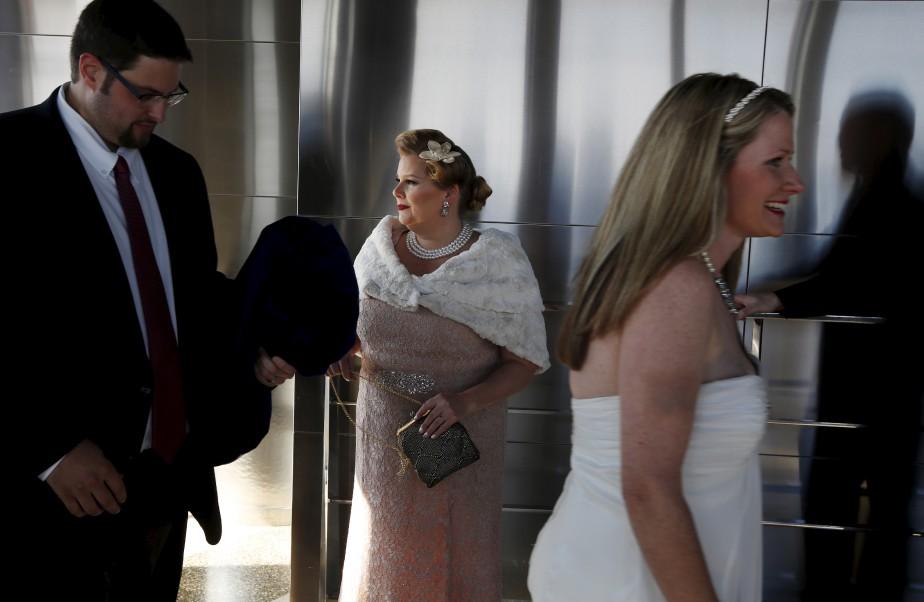 Catherine Fiehn LeStrange, au centre, attend son tour pour sa cérémonie de mariage, alors qu'un autre couple sort tout juste de la sienne. Une dizaine de mariages de la Saint-Valentin étaient prévus en haut de l'Empire State Building, à New York. | 14 février 2017