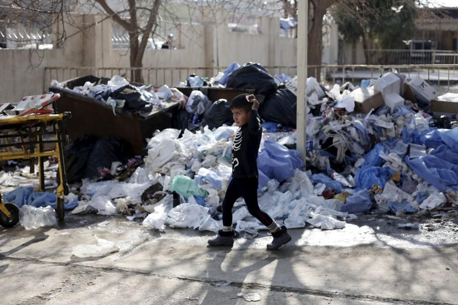 Un enfant blessé à la tête marche devant un tas de déchets à un hôpital de Mossoul, en Irak. Les employés qui traitent les blessés suite aux batailles contre l'État Islamique affirment que le gouvernement n'offre aucune aide sanitaire alors que les déchets s'empilent à vue d'oeil dans les rues. | 14 février 2017