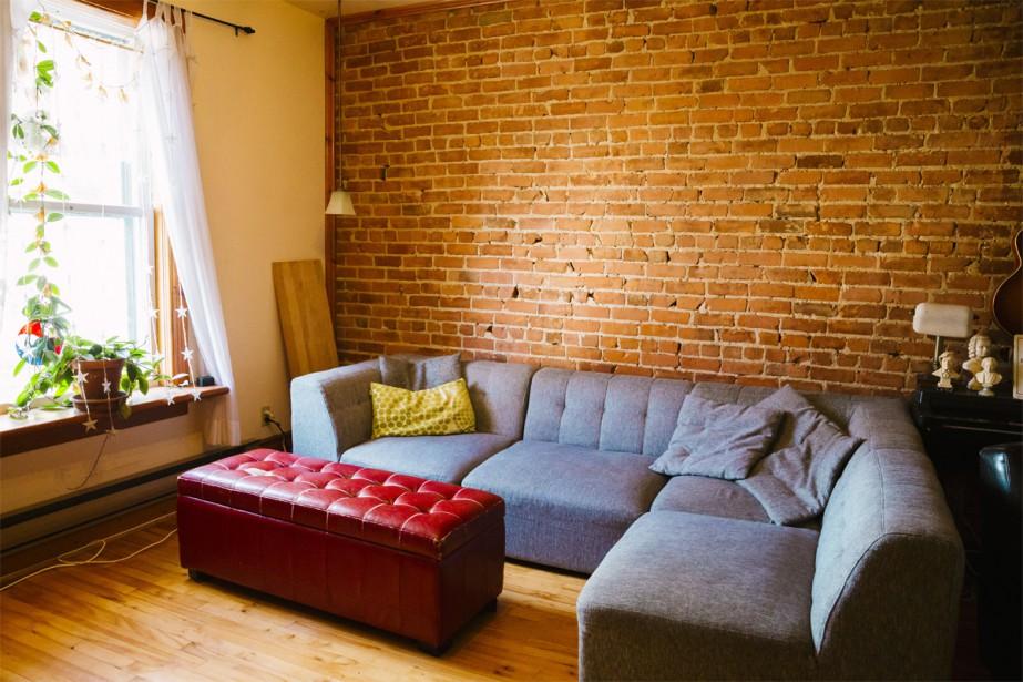 Le salon est une pièce très chaleureuse où l'on se sent bien, entouré de bois et de brique rouge. C'est d'ailleurs le lieu de rassemblement de la famille, qui aime s'entasser sur le grand sofa et où les enfants aiment jouer sur une tablette ou se chamailler, selon les jours! | 15 février 2017