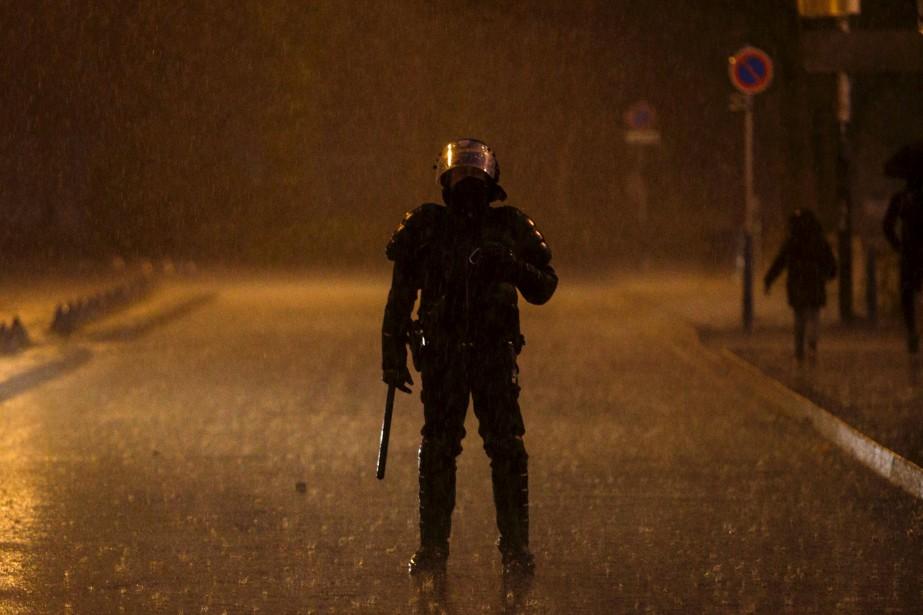 Un policier anti-émeute tient la garde alors que des manifestants se regroupent à Bobigny, en France. Ces derniers réclament justice pour Théo, un jeune travailleur noir de 22 ans qui a eu besoin d'une chirurgie après son arrestation la semaine dernière. Le président français François Hollande a aussi demandé «justice» dans l'affaire, qui inclut un présumé viol à l'aide d'une matraque de police et qui a provoqué 10 nuits d'émeute et plus de 200 autres arrestations. | 16 février 2017