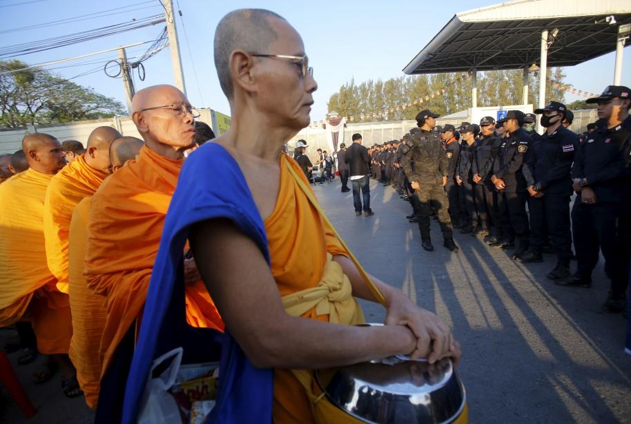 Des moines bouddhistes se tiennent devant les policiers, aux portes du temple Wat Dhammakaya, en Thaïlande, dans lequel est réfugié un chef de secte controversé qui fait l'objet d'une accusation pour avoir accepté 40 millions $ US en argent issu de la criminalité. | 16 février 2017