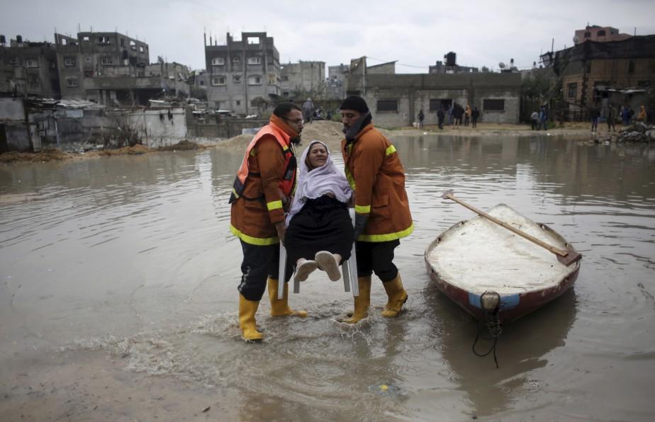 Des secours palestiniens évacuent une femme de sa maison inondée lors d'une pluie torrentielle au camp de réfugiés Jabaliya, dans le nord de la bande de Gaza. | 16 février 2017
