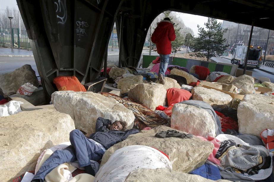 Un migrant dort sous un pont ferroviaire à Paris, alors que des groupes humanitaires affirment que ces rochers controversés empêchent les migrants de s'installer à cet endroit qui a toujours été un refuge pour des citoyens de la Terre qui fuient la guerre et la pauvreté. | 16 février 2017