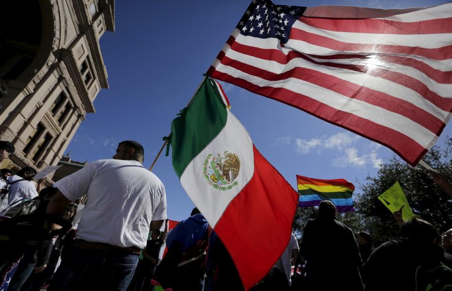 Un manifestant tient les drapeaux américain et mexicain pendant une marche en l'honneur des immigrants. Les immigrants partout à travers les États-Unis se sont absentés du travail, jeudi, pour prouver leur importance au sein de l'économie et du mode de vie américain. Plusieurs commerces sont restés fermés par solidarité dans le cadre de ce «Jour sans immigrants». | 16 février 2017