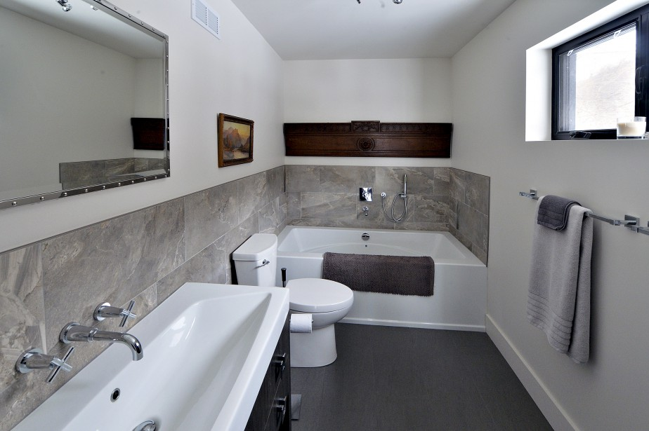 La salle de bain à l'étage. La belle pièce de bois est la devanture d'un lit bateau. Un autre morceau du lit sera installé dans la chambre d'amis en face. (Le Soleil, Patrice Laroche)