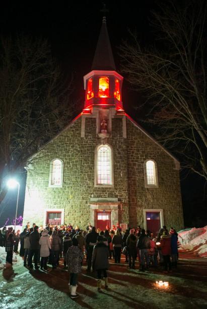 Sous la lueur des bougies tenues par les gens présents à la vigile, l'abbé François Doucet, curé de la paroisse, a d'abord invité son auditoire à la prière sous le son des cloches de l'église. (Olivier Croteau, Le Nouvelliste)
