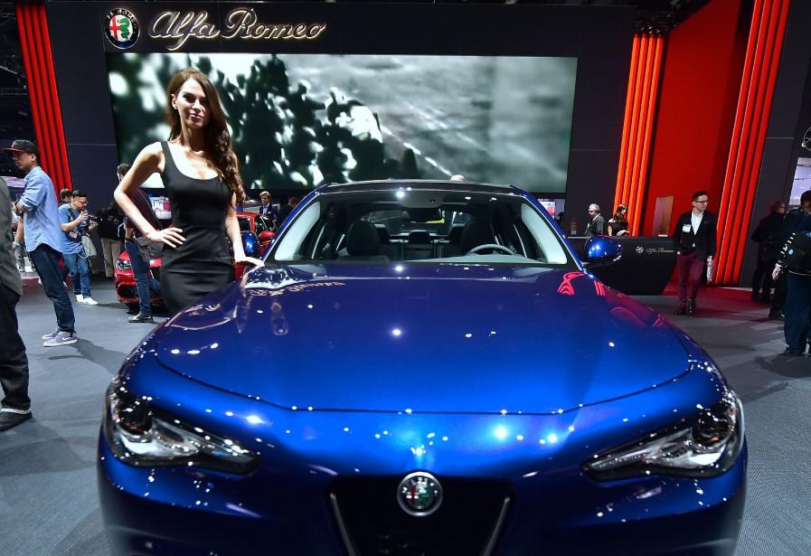 Une hôtesse pose aux côtés de l'Alfa Romeo Giulia au Salon de l'auto de Los Angeles en novembre 2016. Elle est en lice pour le titre de voiture européenne de l'année au Salon de l'auto de Genève. (AFP)