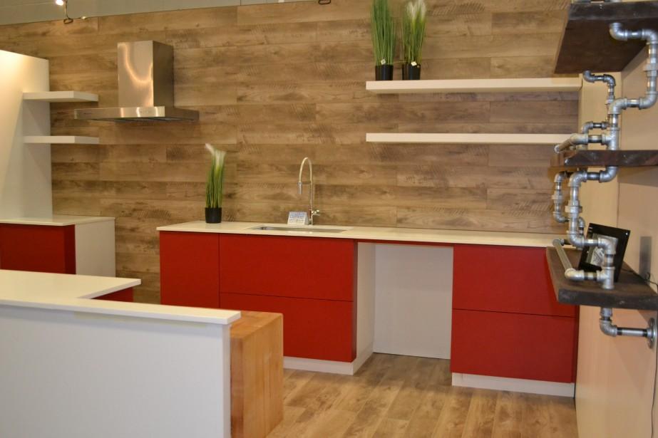 Armoires Deluxe a fait équipe avec la Boutique Eau Saguenay pour créer un magnifique espace présentant deux cuisines différentes ainsi qu'un modèle de lit escamotable. Sur cette photo, on peut observer les jolies tablettes murales faites avec des tuyaux. Agencées avec la cuisine aux accents de rouge, modernisme et style industriel font bon ménage. (Claudie Laroche)