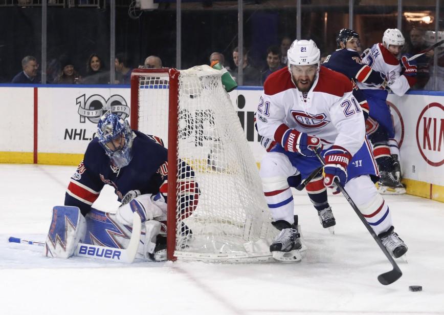 Dwight King tente de déjouer Henrik Lundqvist en contrôlant la rondelle de l'arrière de sa cage. (Photo Julie Jacobson,  AP)