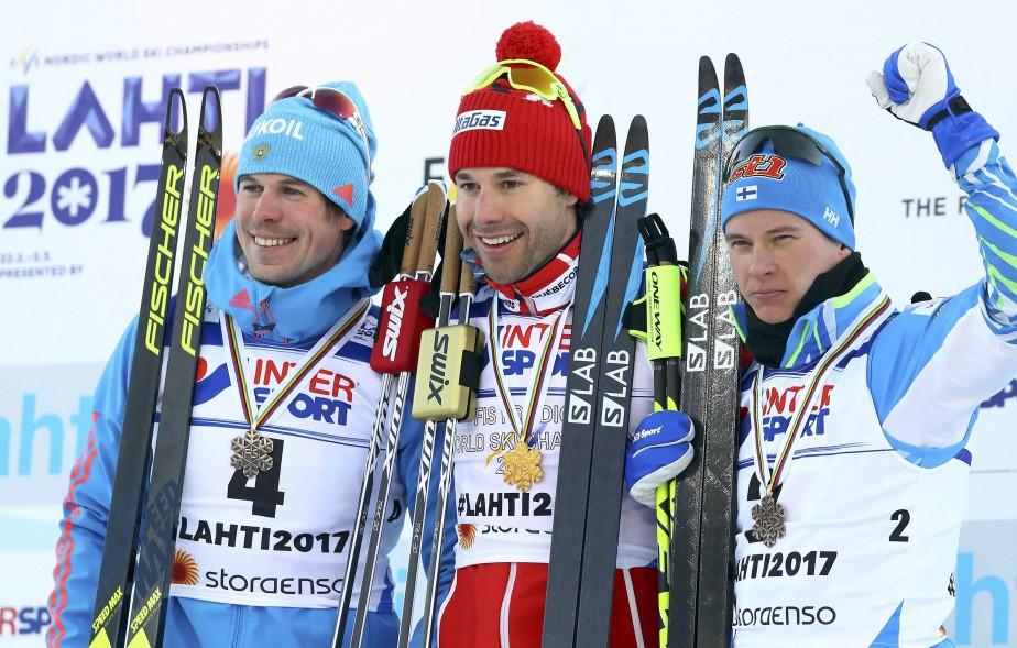 Le Russie Sergey Ustiugov (à gauche) et le Finlandais Mati Heikkinen accompagnaient le champion sur le podium. (Photo Kai Pfaffenbach, REUTERS)