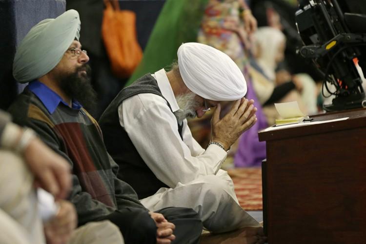 Des hommes prient dans un temple sikh, dimanche,... (PHOTO AP)