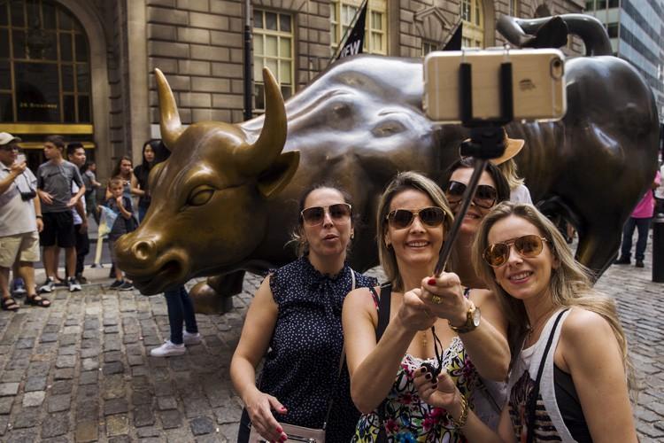 Des touristes visitent Wall Street, à Manhattan.... (ARCHIVES REUTERS)