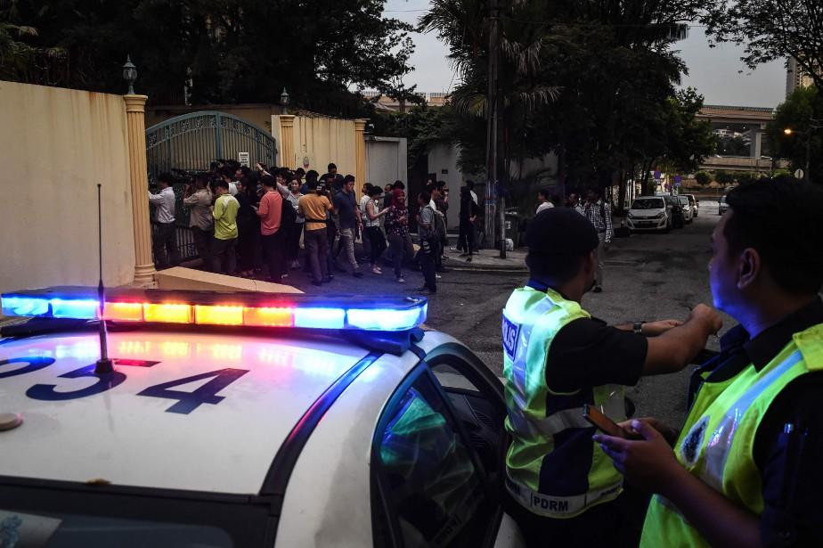 Des policiers malaisiens surveillent des membres des médias... (AFP)