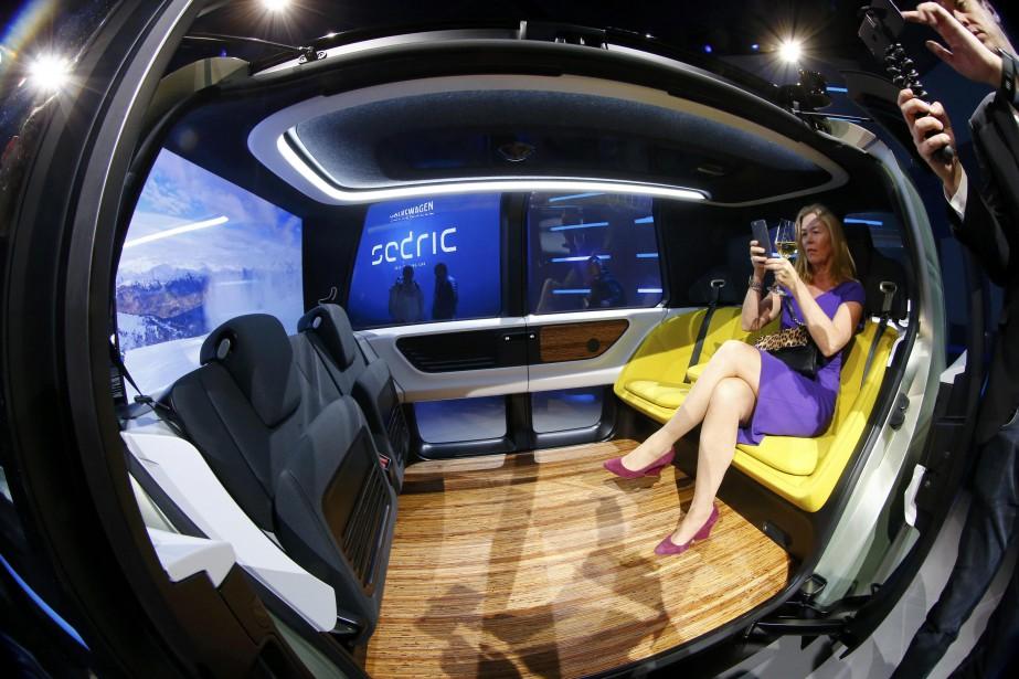Une journaliste prend des photos à l'intérieur du prototype devéhicule électrique autonome Sedric, au Salon de l'auto de Genève. (REUTERS)