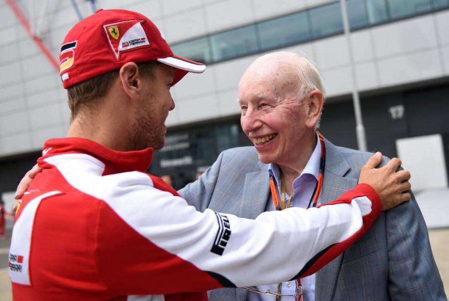 Sebastian Vettel salue l'ancien pilote de moto et de F1 dans le paddock Ferrari avant le GP de Grande-Bretagne le 15 juillet 2015. Surtees a été champion du monde de F1 pour Ferrari en 1964. (AFP)