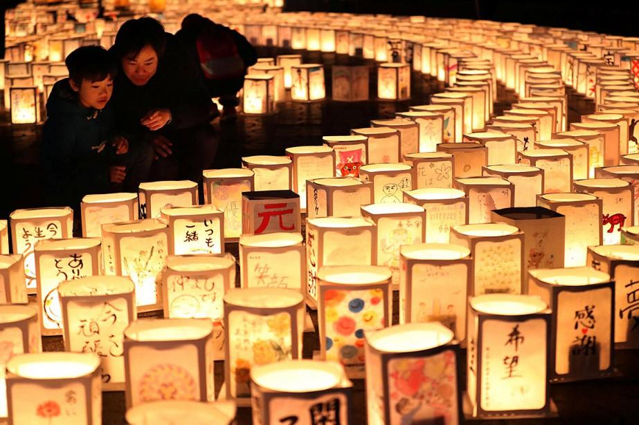 Une famille regarde des lanternes en papier regroupées... (PHOTO REUTERS/Kyodo)