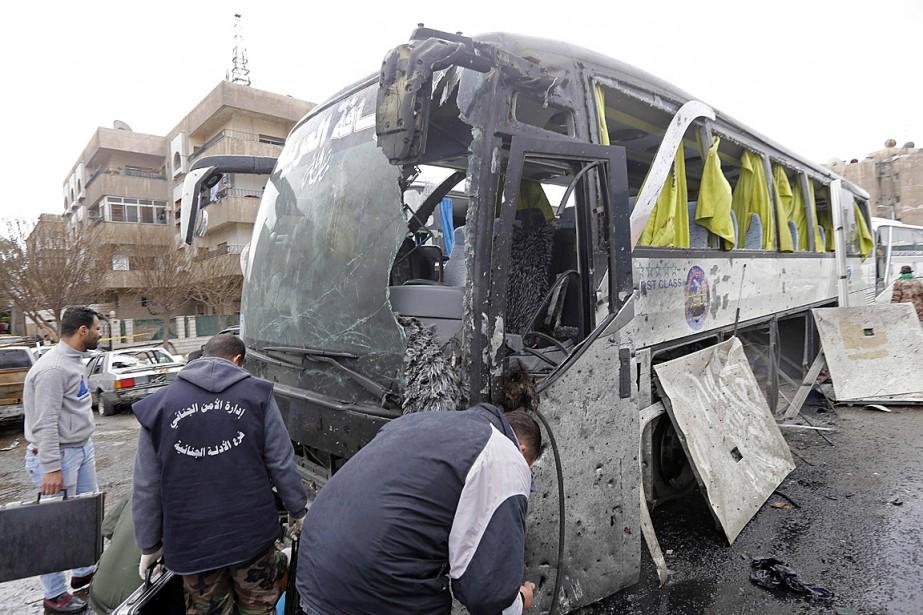 Des enquêteurs examinent un autobus endommagé lors du... (AFP, Louai Beshara)