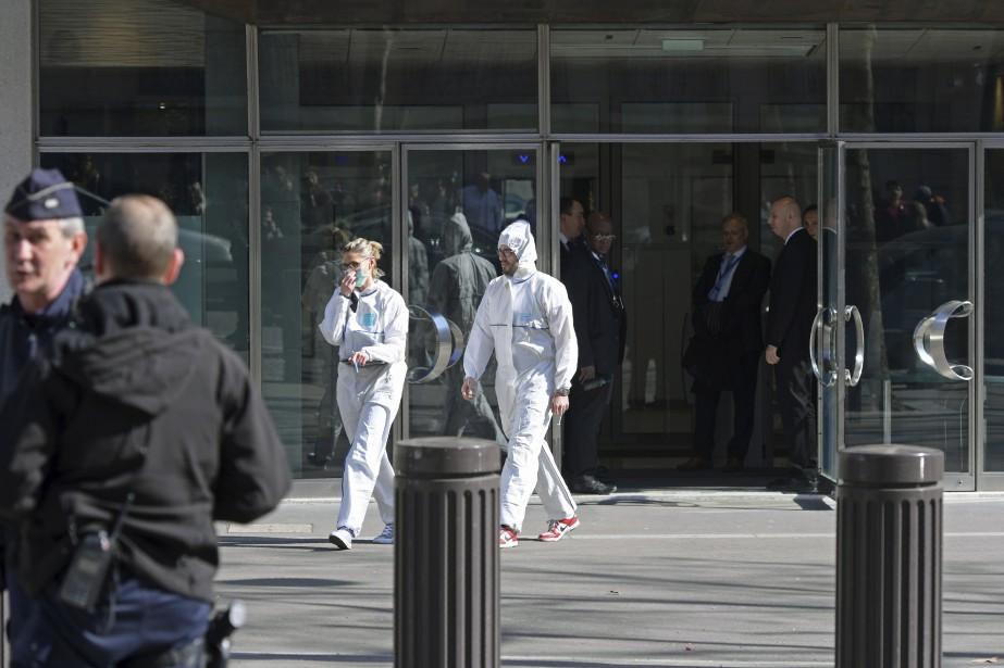 Des experts médico-légaux ressortent des bureaux du Fonds monétaire international (FMI), où une lettre-bombe a explosé et blessé une employée. | 16 mars 2017