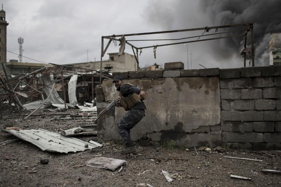 Un officier de la police fédérale irakienne se met à l'abri lors d'une bataille contre le groupe armé État islamique. | 16 mars 2017