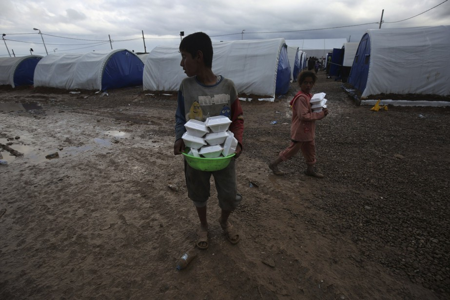 De jeunes Irakiens déplacés transportent des rations jusqu'à leurs familles au camp Hammam al-Alil, au sud de Mossoul. | 16 mars 2017