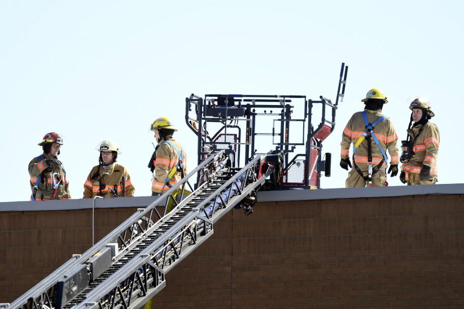 Des pompiers sur le toit du centre commercial. (PHOTO BERNARD BRAULT, LA PRESSE)