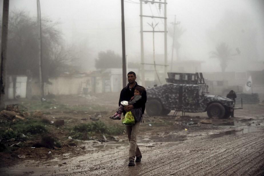 Un homme transporte son enfant alors qu'il fuit la zone de combat entre les forces irakiennes et les combattants de l'État islamique, dans l'ouest de Mossoul.  | 17 mars 2017