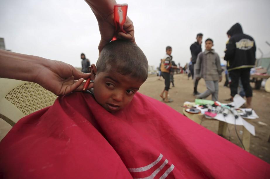 Un jeune Irakien reçoit une coupe de cheveux dans le camp de réfugiés Hammam al-Alil. | 19 mars 2017