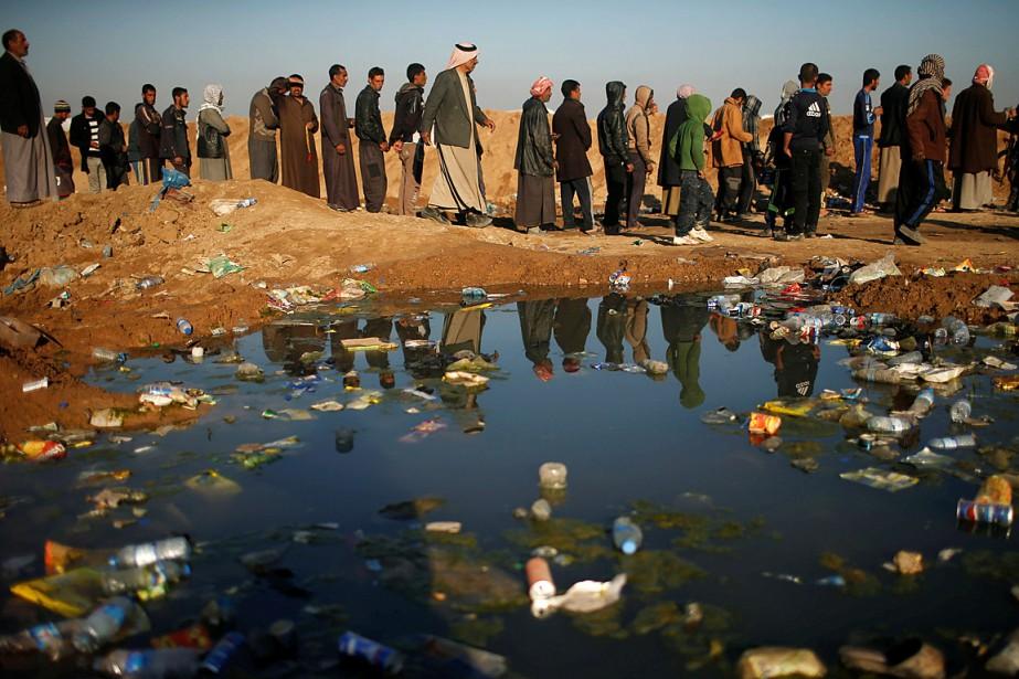Des déplacés irakiens patientent pour entrer au camp... (Photo Suhaib Salem, REUTERS)