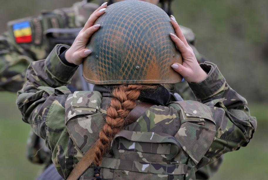 Une soldate roumaine ajuste son casque pendant un entraînement avec ses collègues féminines des US Marines, sur les côtes de la mer Noire. | 20 mars 2017