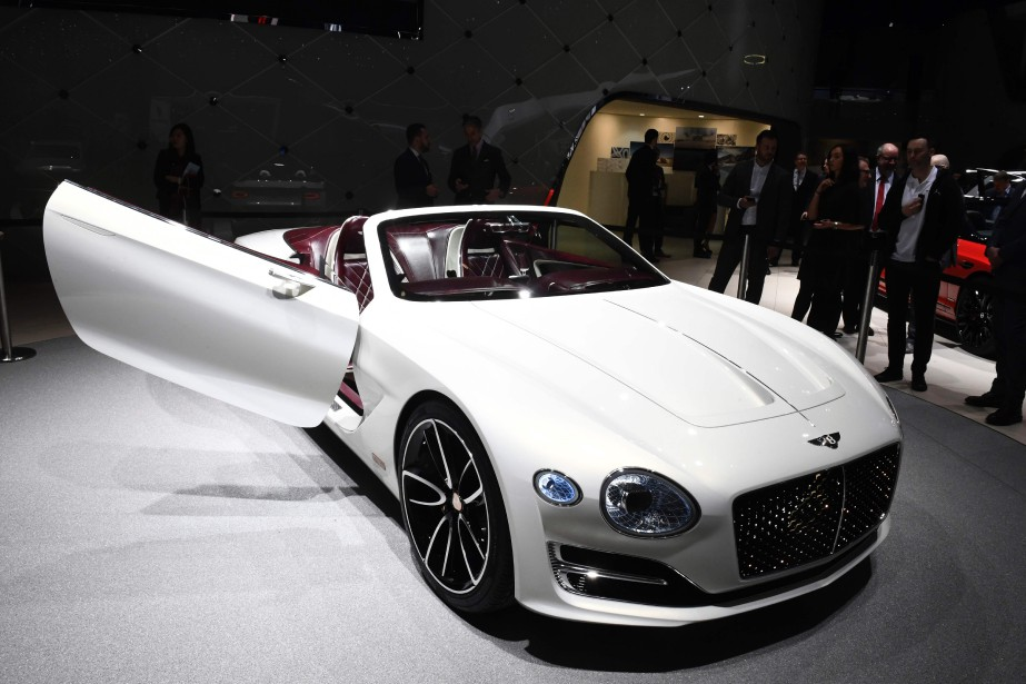 People gather next to a Bentley EXP 12...