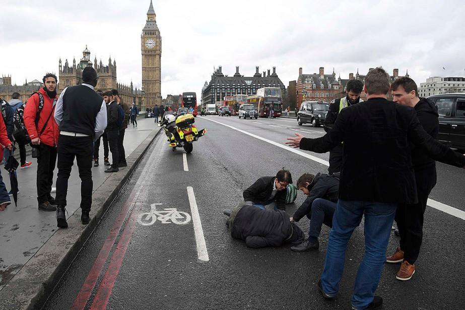 Des passants interviennent auprès d'un blessé. (Photo Toby Melville, Reuters)