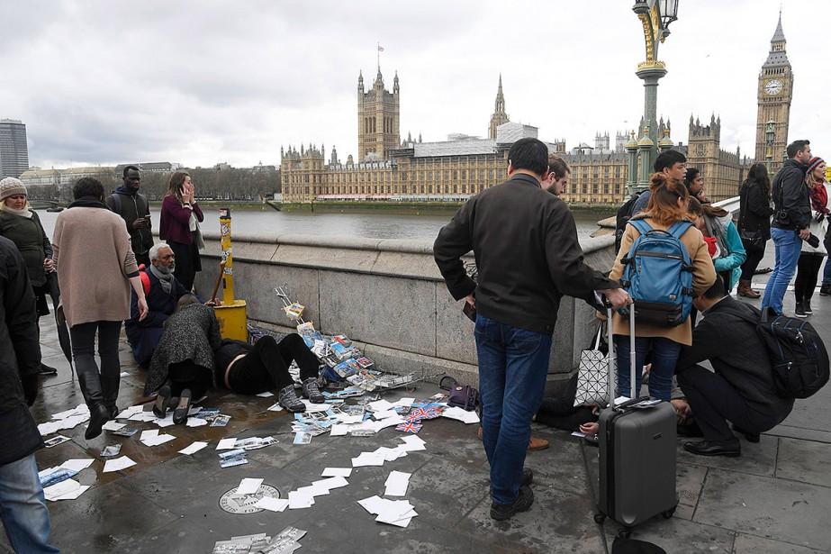 Des personnes aident des blessés, sur le pont de Westminster, à Londres. (Photo Toby Melville, REUTERS)