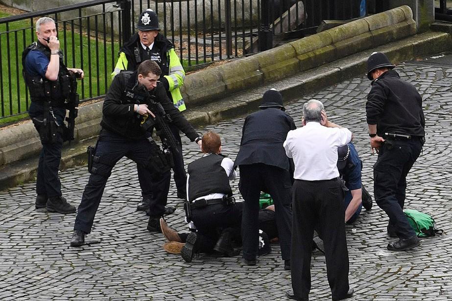 Un policier pointe son arme sur un homme au sol. | 22 mars 2017