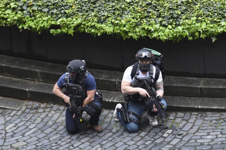 Deux policiers armés sont sur le qui-vive près du parlement britannique. | 22 mars 2017