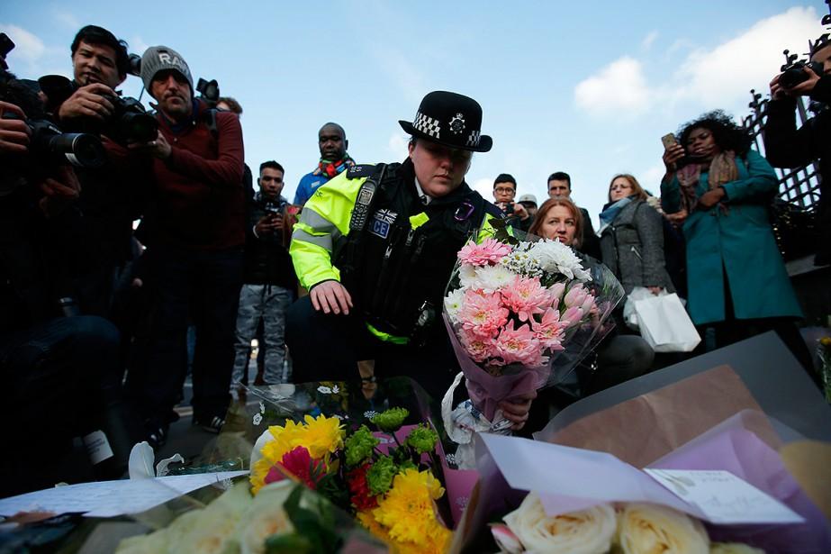 Des gens déposent des fleurs à la suite... (Daniel LEAL-OLIVAS, AFP)