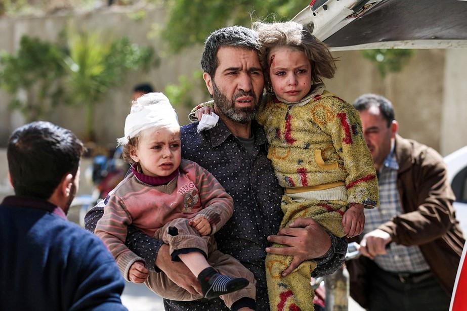 Un homme porte deux enfants après une frappe... (PHOTO AMER ALMOHIBANY, AGENCE FRANCE-PRESSE)