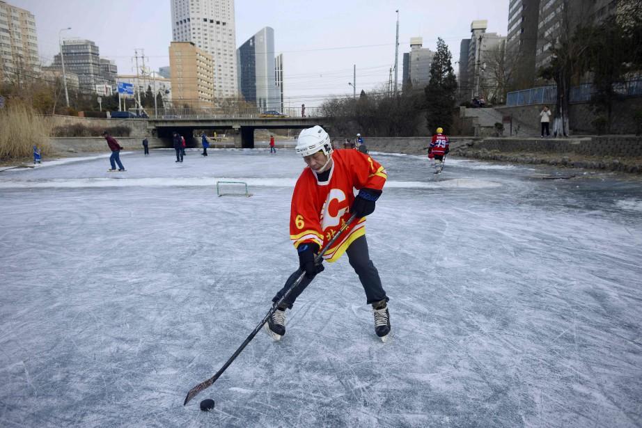 Un homme joue au hockey sur une rivière... (ARCHIVES AFP)